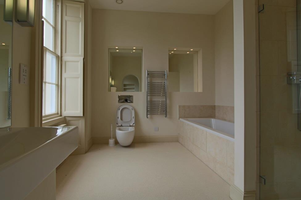 En suite 11 11 x 10 4 Panelled bath, wc with concealed cistern, sink and handbasin, shuttered windows to rear  Bedroom