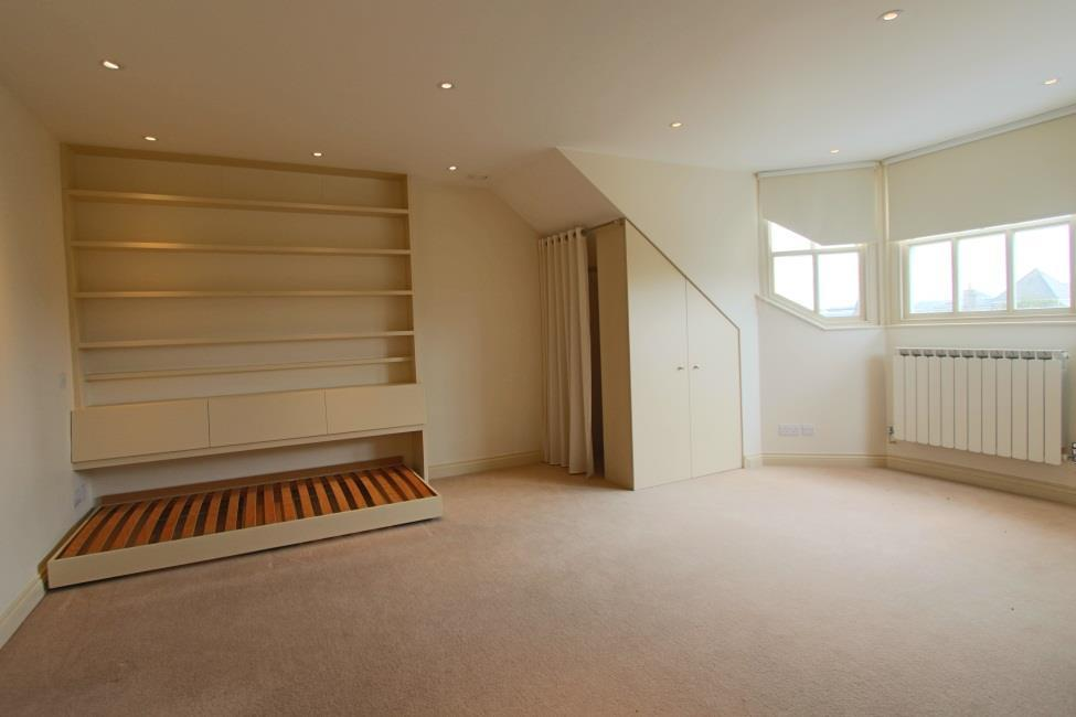 Bedroom 5 18 11 x 15 7 Built in cupboards with curtained storage areas with rail.