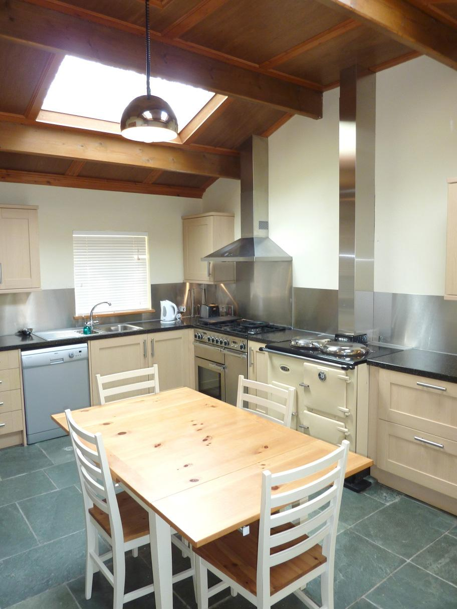 Granite style laminate worksurface with 1 ½ bowl stainless steel sink and drainer. Rangemaster 5 ring gas hob range cooker with Rangemaster overhead extractor. Esse stove.