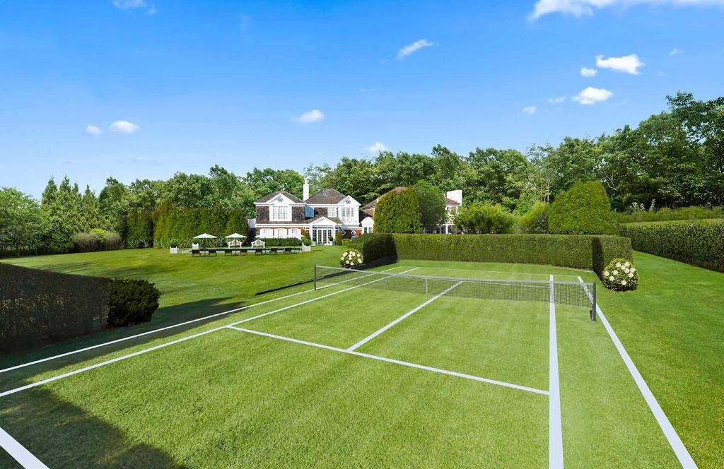 Back Exterior The back exterior features sprawling lawns and mature gardens, with a heated gunite swimming pool, a grass tennis court,