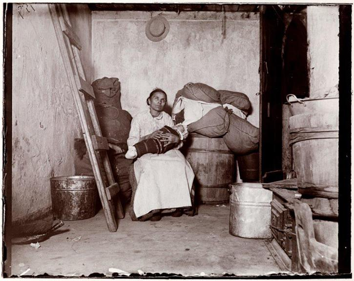 Document C This image shows an Italian immigrant and her baby sitting in their windowless oneroom tenement.