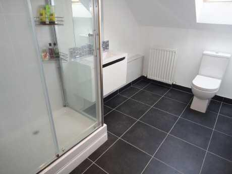Shower room Velux window to front aspect, fitted storage cupboards, white suite comprising low flush WC, floating wash hand basin with vanity unit under, shower cubicle with