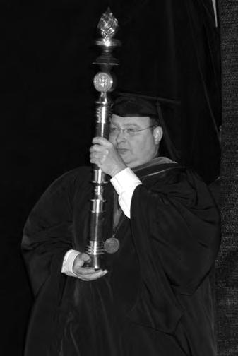 PRESIDENTIAL MACE CROWNED BY A FLAME symbolizing the Light of Knowledge, the Texas Tech University Presidential Mace is the symbolic staff of the power and authority of the university.