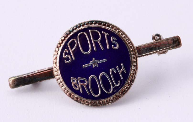In 1971 the brooch was changed from its original art deco design of a circular centre of royal blue enamel with BGGS gold lettering and gold sides extending out each side to points, to a circular