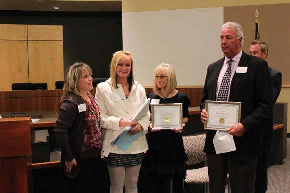 parents who received the award for him, presented by Lisa Secca (left) The