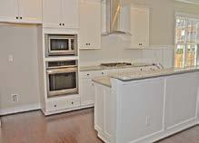 stained raised panel wood cabinets in Kitchen with cushion close &