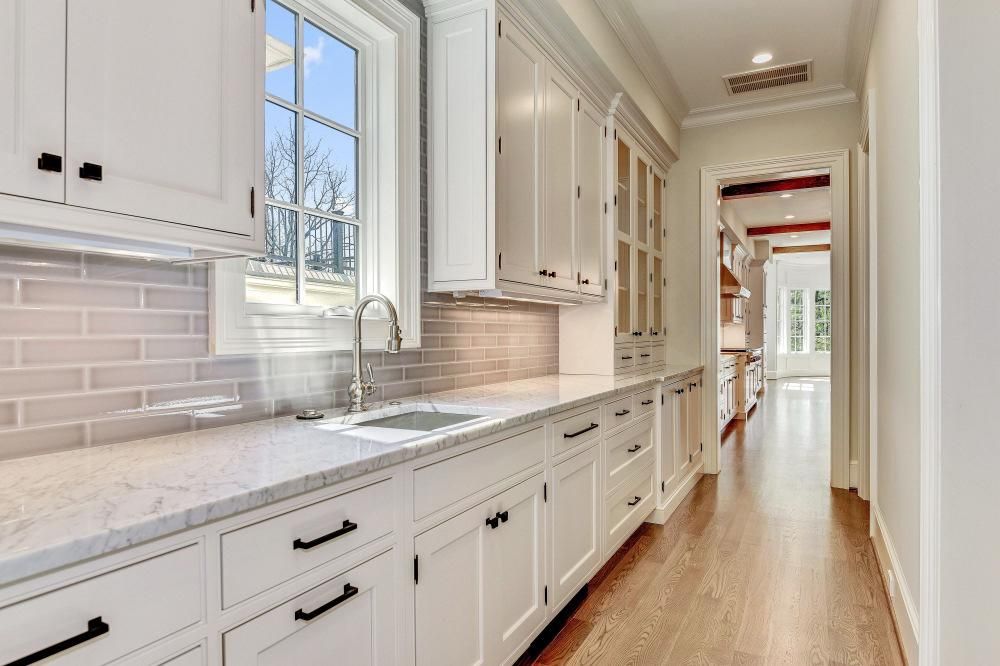 stunning screened-in porch with gorgeoius finishes & additional gas fireplace Formal dining room with tray ceiling and conveniently located butler's pantry with built-in dishwasher, sink & ample