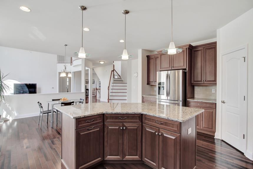 Granite countertops perfectly coordinate with the warm wood hues of the cabinetry and offer great space for food prep and