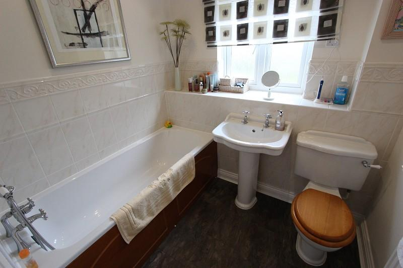 mprising of bath with shower head over, w.c. and wash hand basin, one radiator, upvc window to rear, half tiled walls.