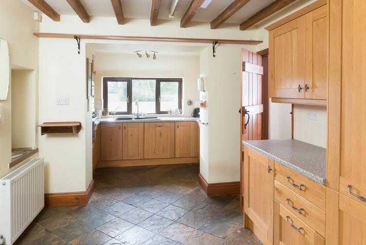 splashbacks, slate floor. Opening to DINING ROOM with tiled floor. UTILITY ROOM with single bowl, single drainer sink unit with monobloc mixer taps over and cupboards beneath.